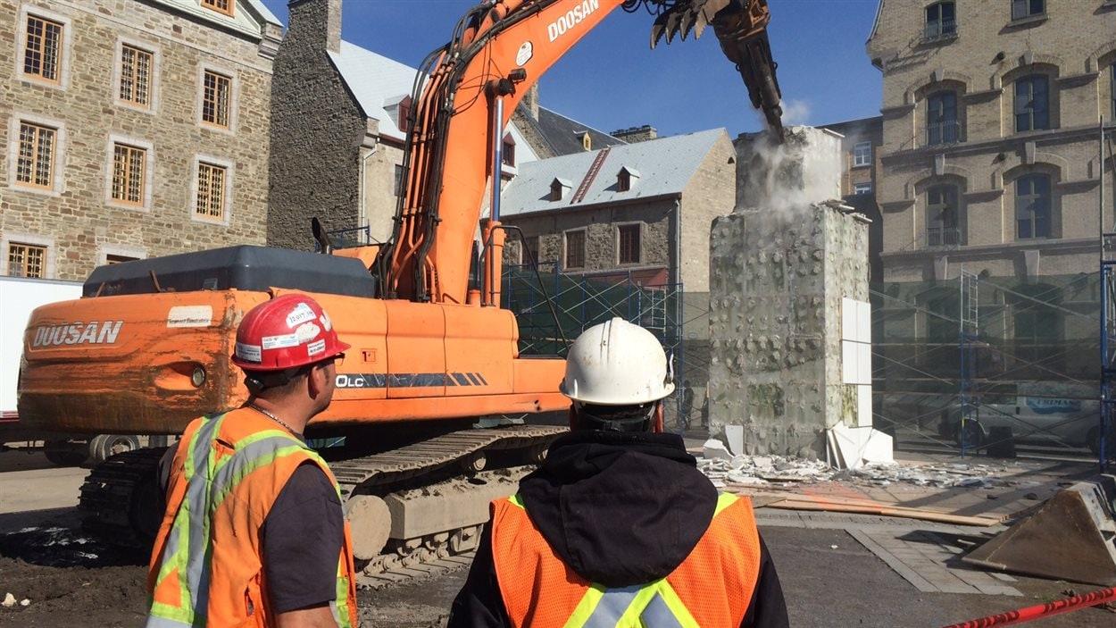 Les ouvriers procèdent à la démolition de l'oeuvre.
