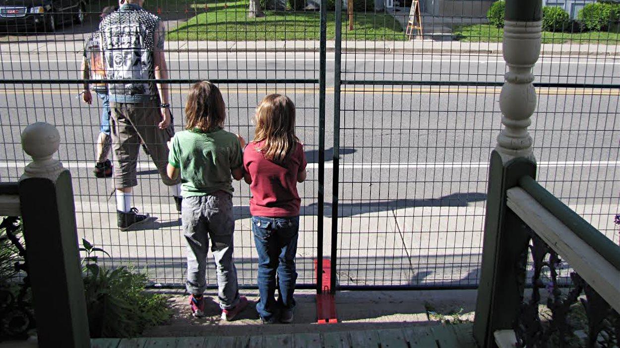 Deux enfants d'Emmanuel Charlebois, derrière les grilles encerclant leur maison, à Montebello, pendant la durée du Rockfest.