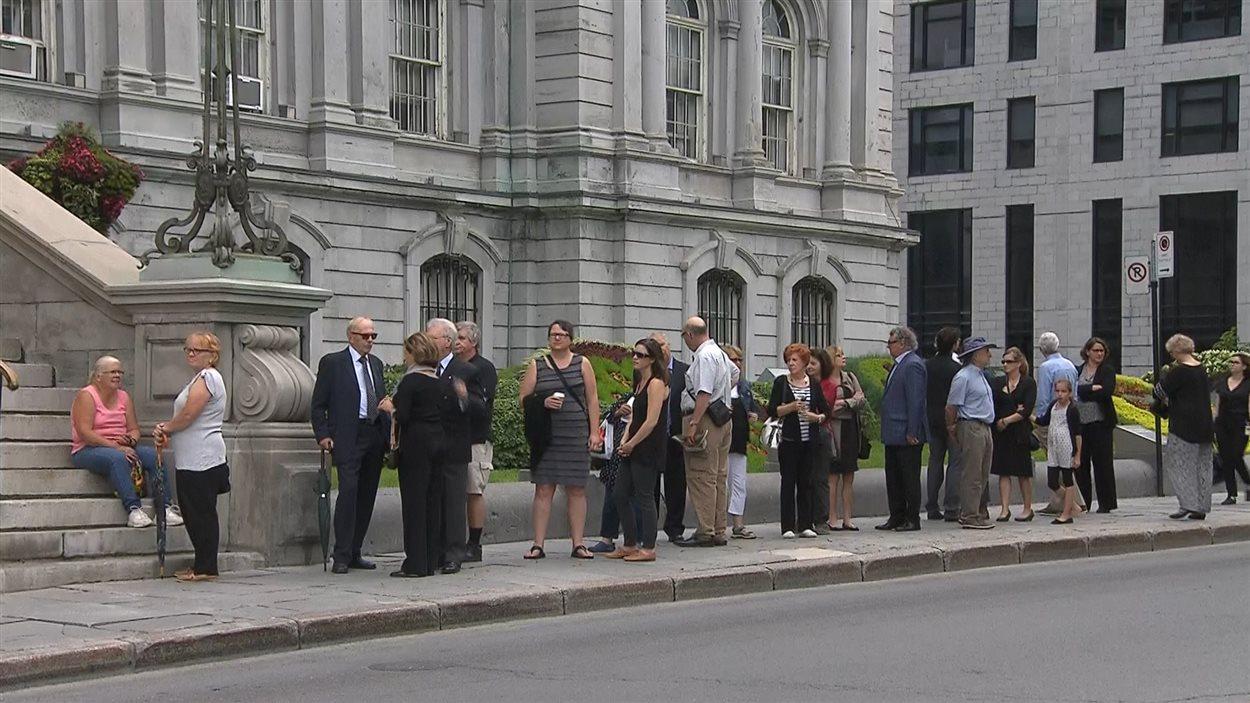 Des citoyens attendent en file avant l'ouverture des portes à l'hôtel de ville, le 21 juin, où la dépouille de l'ancien maire Jean Doré est exposée en chapelle ardente.