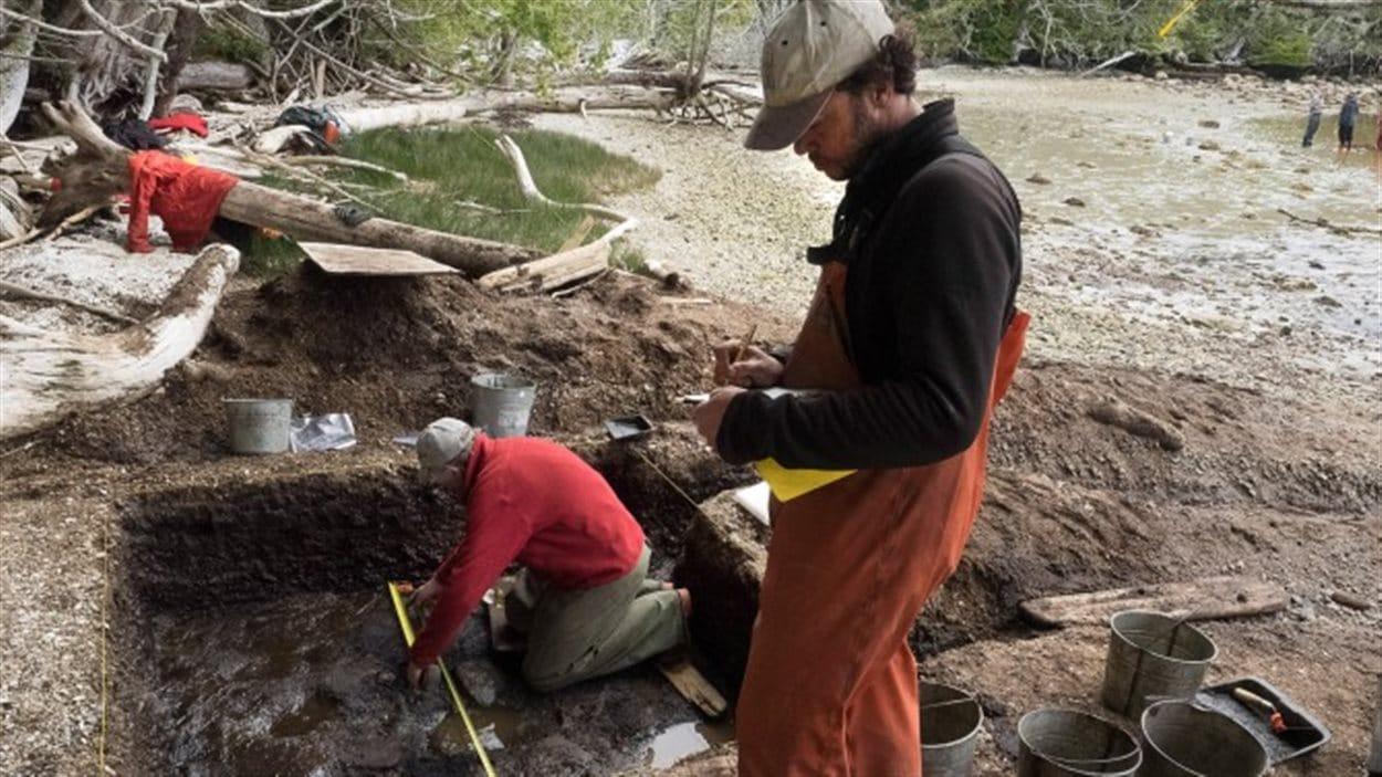 Daryl Fedge (agenouillé) et Duncan McLaren, archéologues de l'Université de Victoria, creusent les sédiments à marée basse