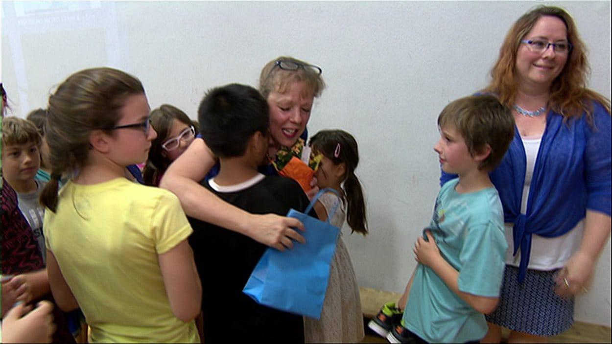 Les élèves de Monique Rousseau lui donnent des derniers câlins.