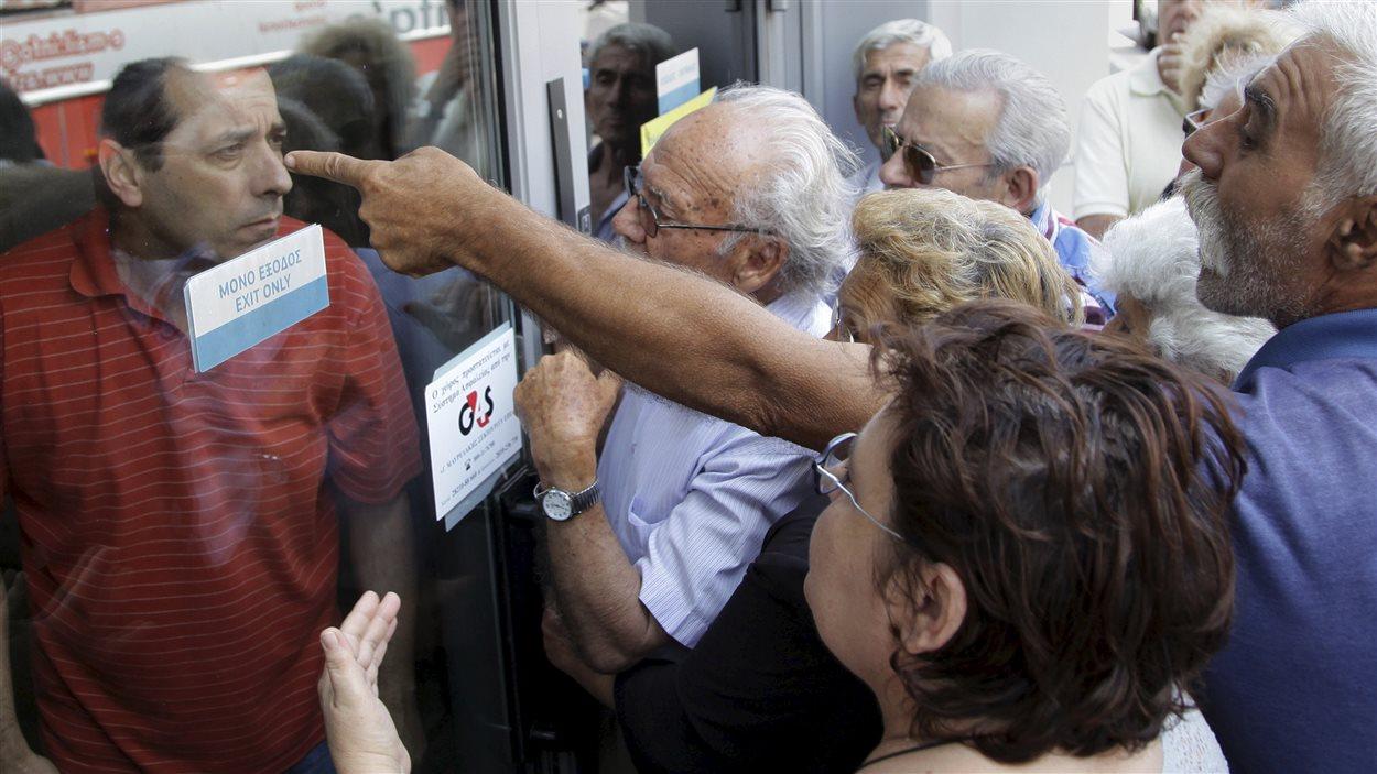 Des retraités devant la succursale d'une banque