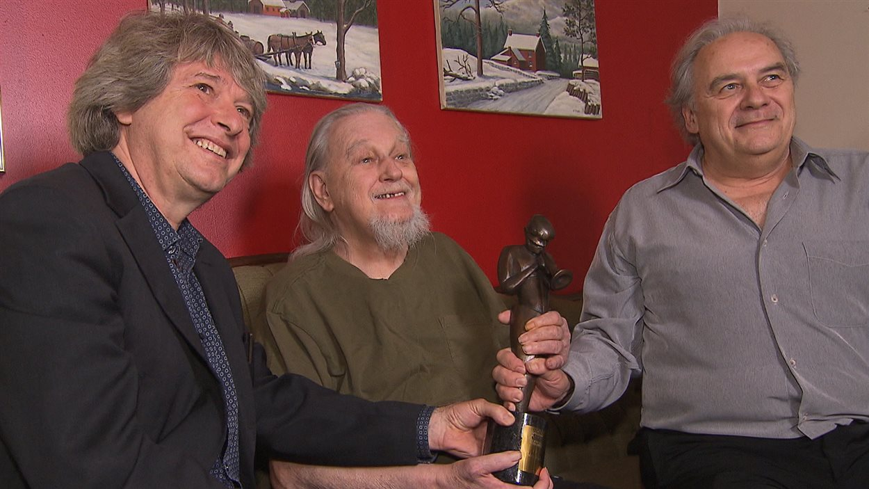 Vic Vogel (au centre) reçoit le prix Miles-Davis des mains d'André Ménard (à droite) et Alain Simard (à gauche), fondateurs de Spectra et du festival du Jazz.