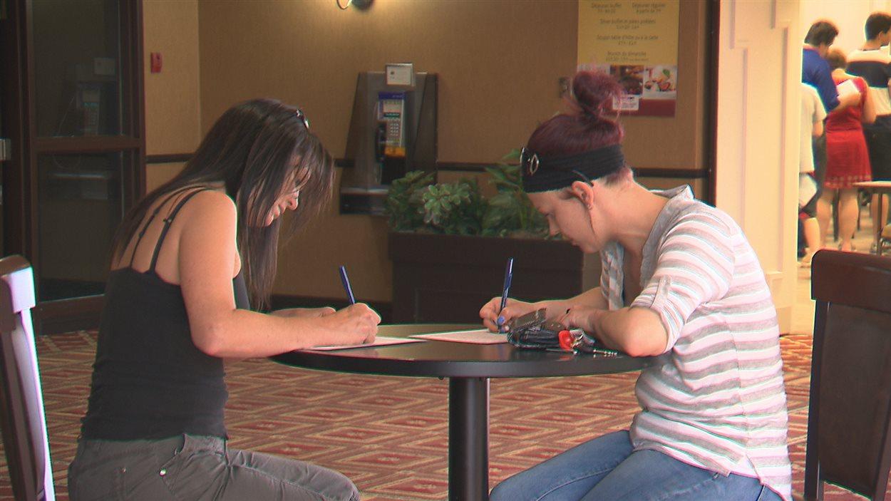 Marie-Josée Duchesne (gauche) et sa soeur Mélissa (droite) remplissent un formulaire avant d'aller à la table de casting.