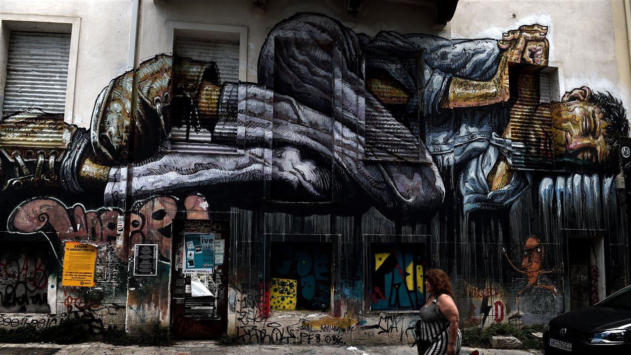 Une murale représentant un sans-abri dans une rue d'Athènes en Grèce.