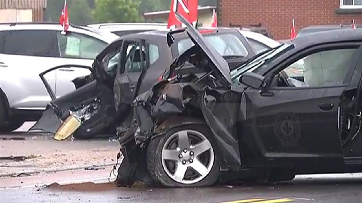 Le véhicule banalisé de la SQ et celui des victimes en arrière-plan témoignent de l'ampleur de l'impact.