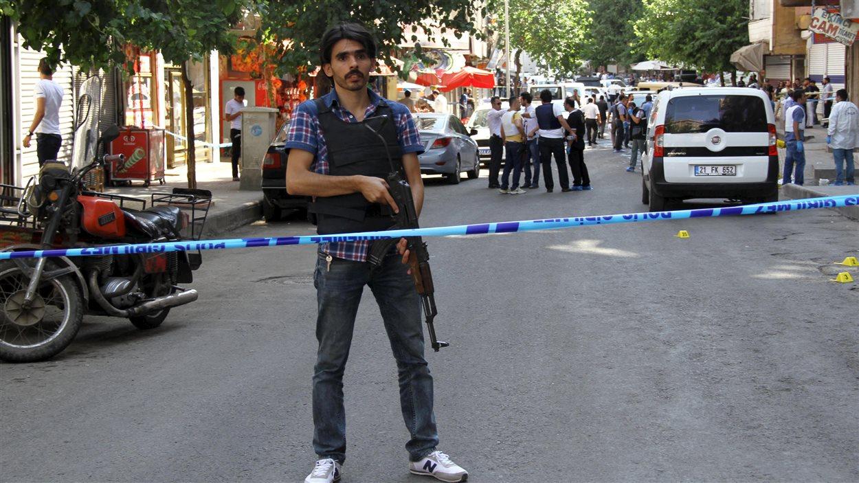 Un policier habillé en civil monte la garde après un attentat survenu près de la ville-frontière turco-syrienne. (23 juillet 2015)