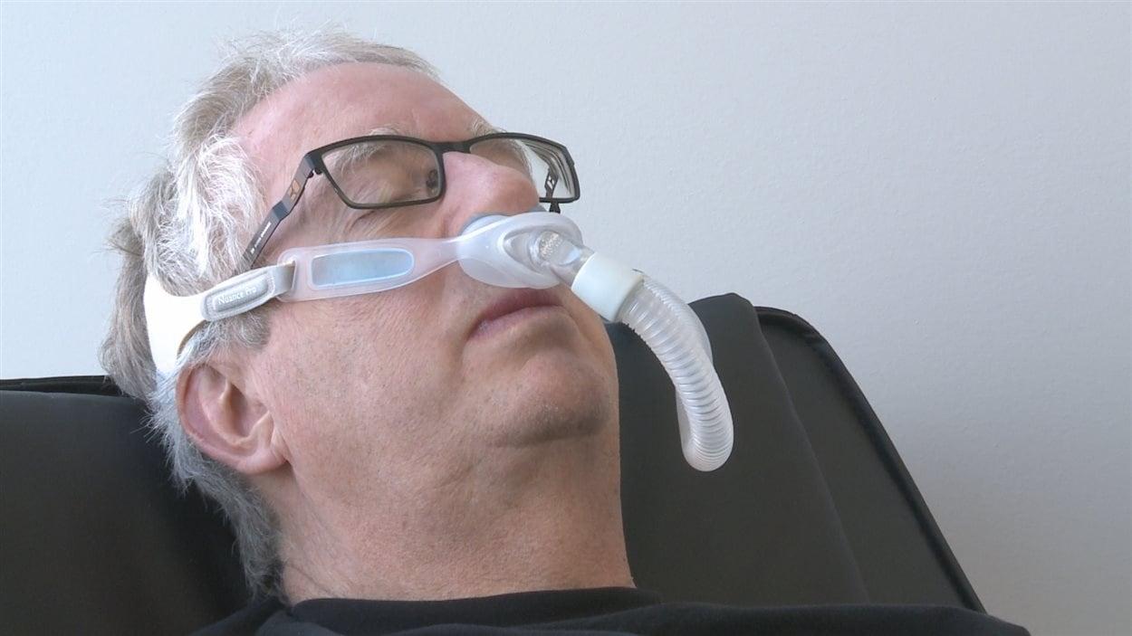 Un patient qui utilise un appareil respiratoire pour traiter l'apnée du sommeil.