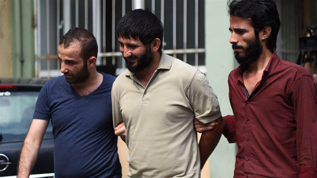 Des policiers habillés en civil escortent un membre suspecté du groupe armé État islamique à l'hôpital, pour un examen médical. (24 juillet 2015)