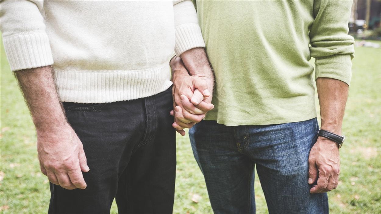 Deux aînés homosexuels main dans la main.