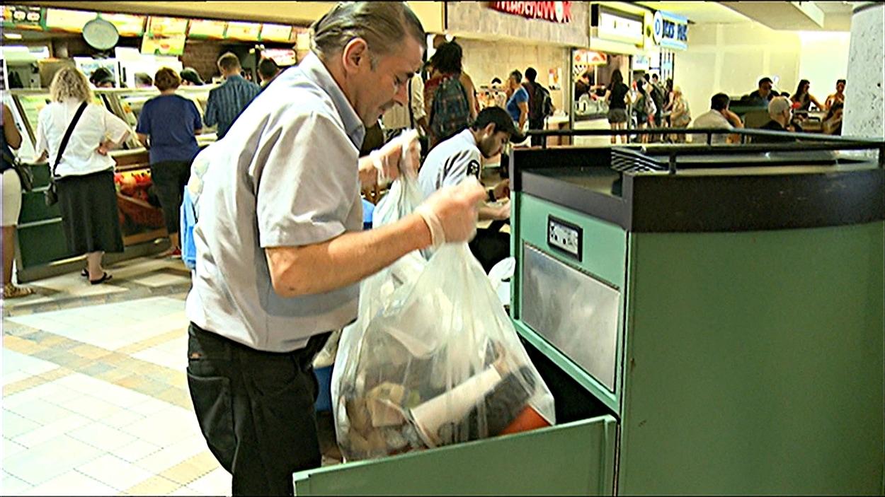 Un concierge vide les poubelles dans un centre commercial d'Ottawa (archives).