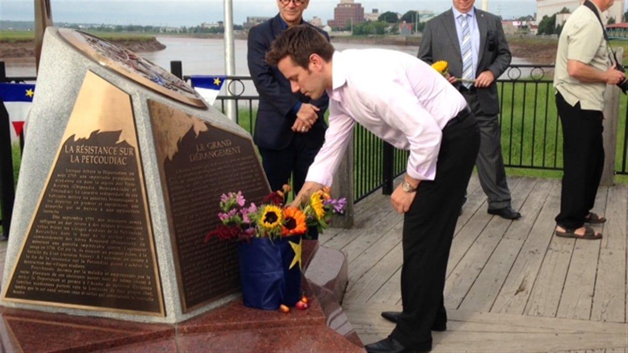 Des fleurs sont déposées au pied du monument.