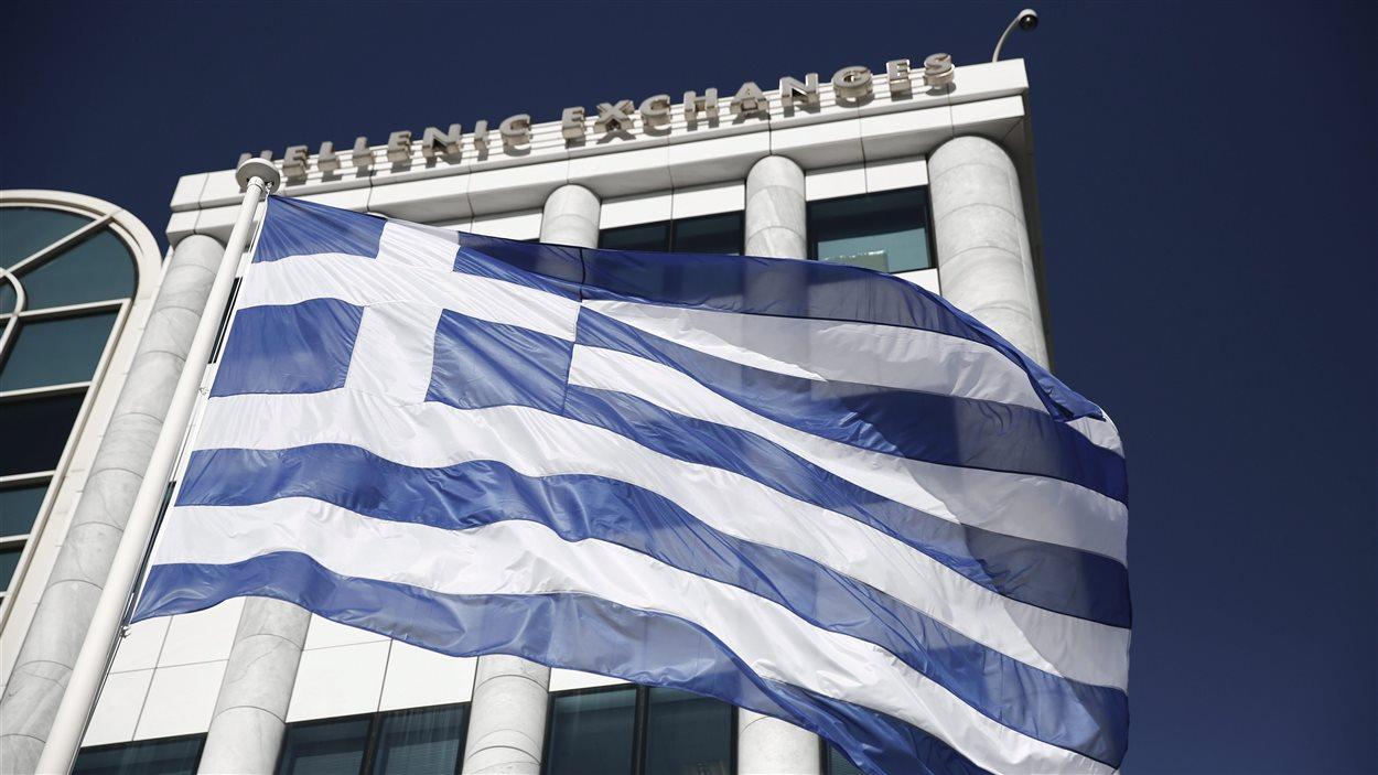 Un drapeau grec lotte devant la Bourse d'Athènes.