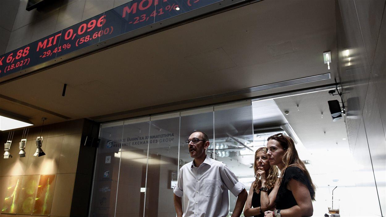 Des employés de la Bourse d'Athènes regardent les prix des actions sur l'écran.