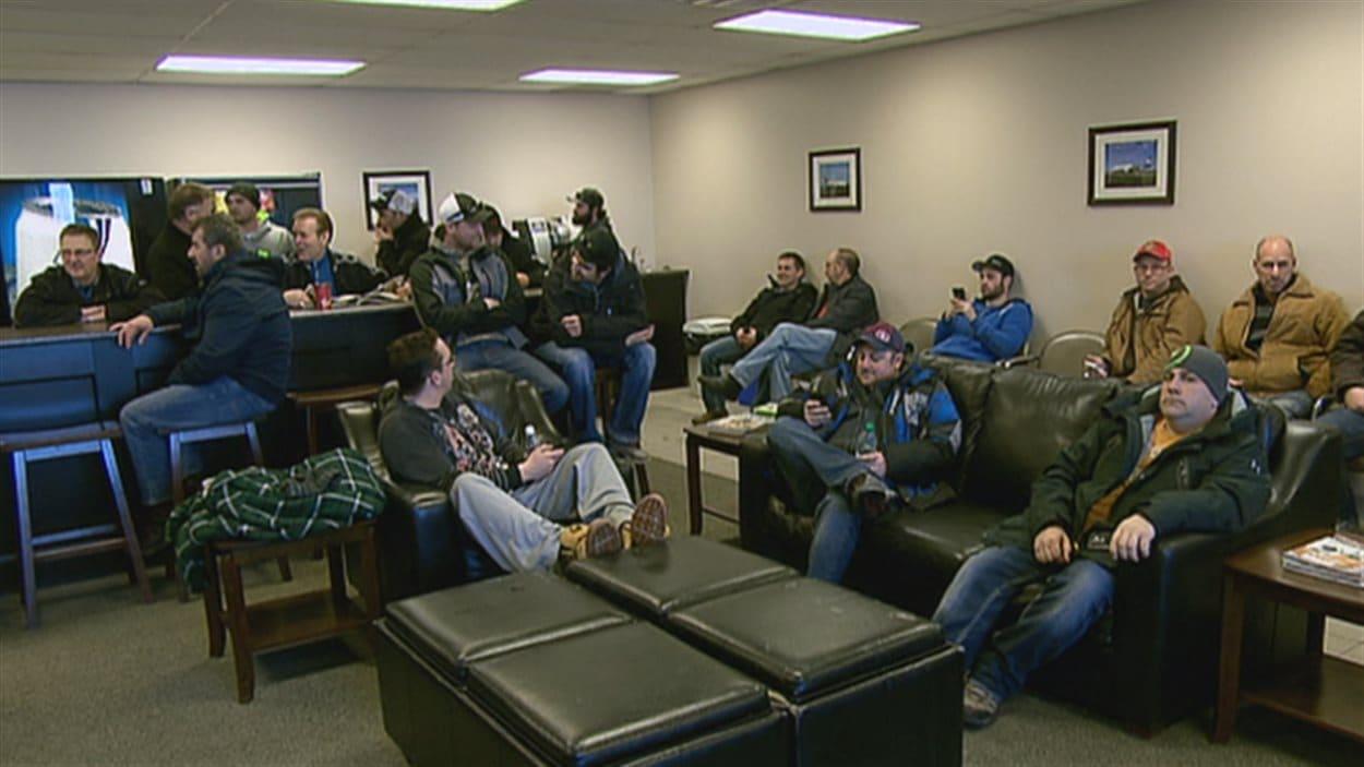 Des Néo-Brunswickois qui partent travailler dans l'Ouest canadien attendent leur vol à l'ancien aéroport de Moncton.