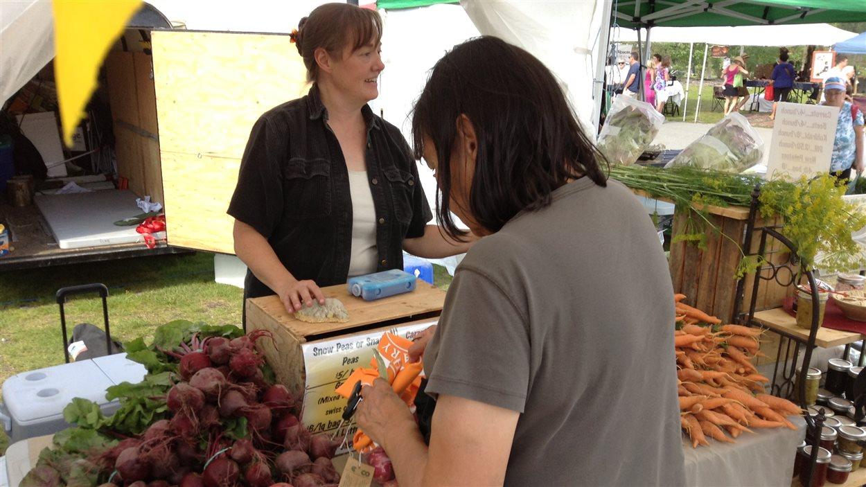 Une cliente achète des légumes d'une agricultrice
