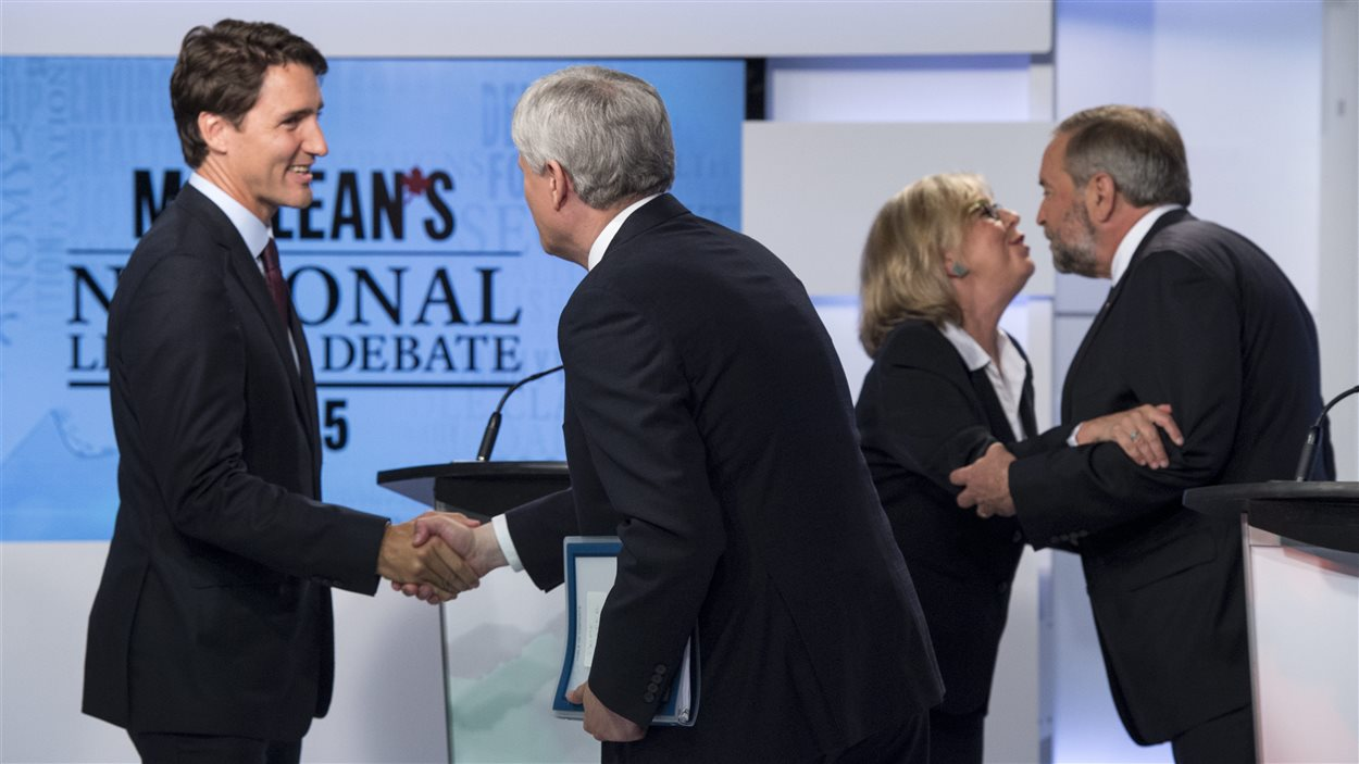 Après le débat, le chef libéral, Justin Trudeau, à gauche, serre la main à Stephen Harper, chef du Parti conservateur et la chef du Parti vert, Elizabeth May, embrasse Thomas Mulcair, chef du Nouveau Parti démocratique.