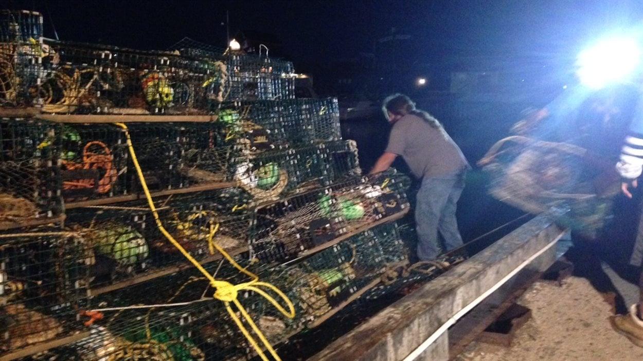 Des pêcheurs chargent des cages à homard sur un bateau.