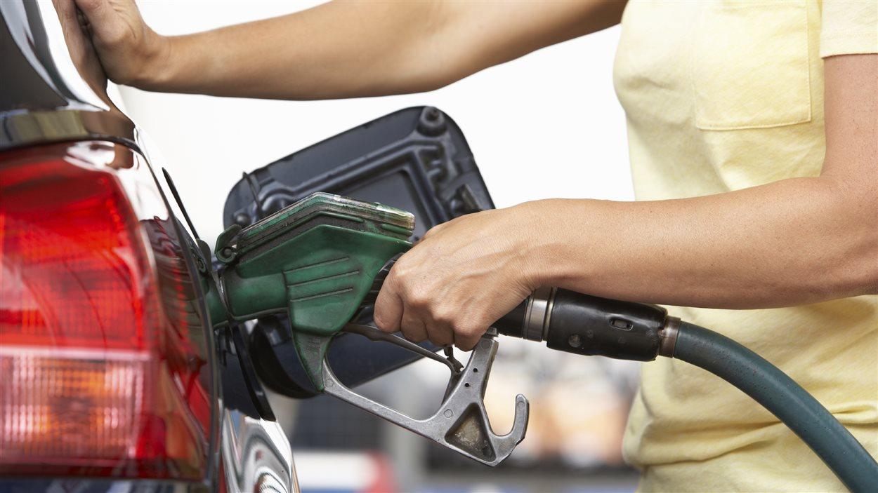 Un femme met de l'essence dans sa voiture.