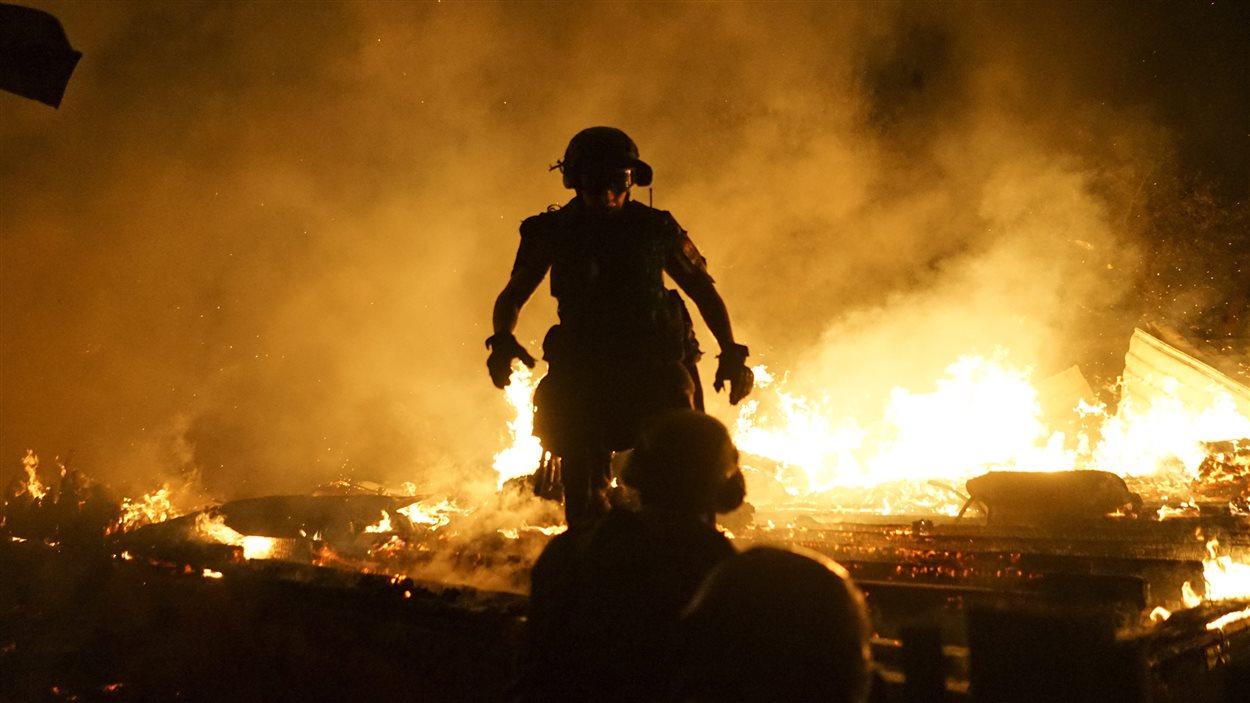 Des pompiers éteignent le feu d'une maison détruite par des bombardements à Donetsk, dans l'est de l'Ukraine