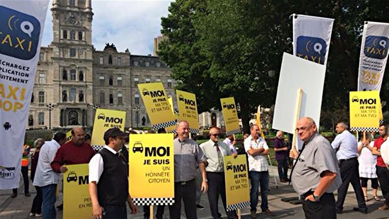 Des chauffeurs de taxi manifestent devant le Parlement à Québec.