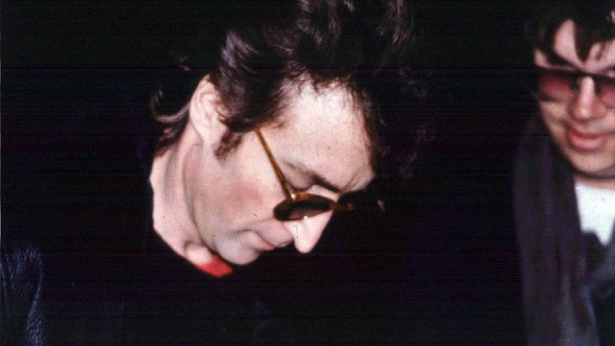 John Lennon autographie un album pour Mark David Chapman (à droite), à la sortie de son appartement de New York le 8 décembre 1980.