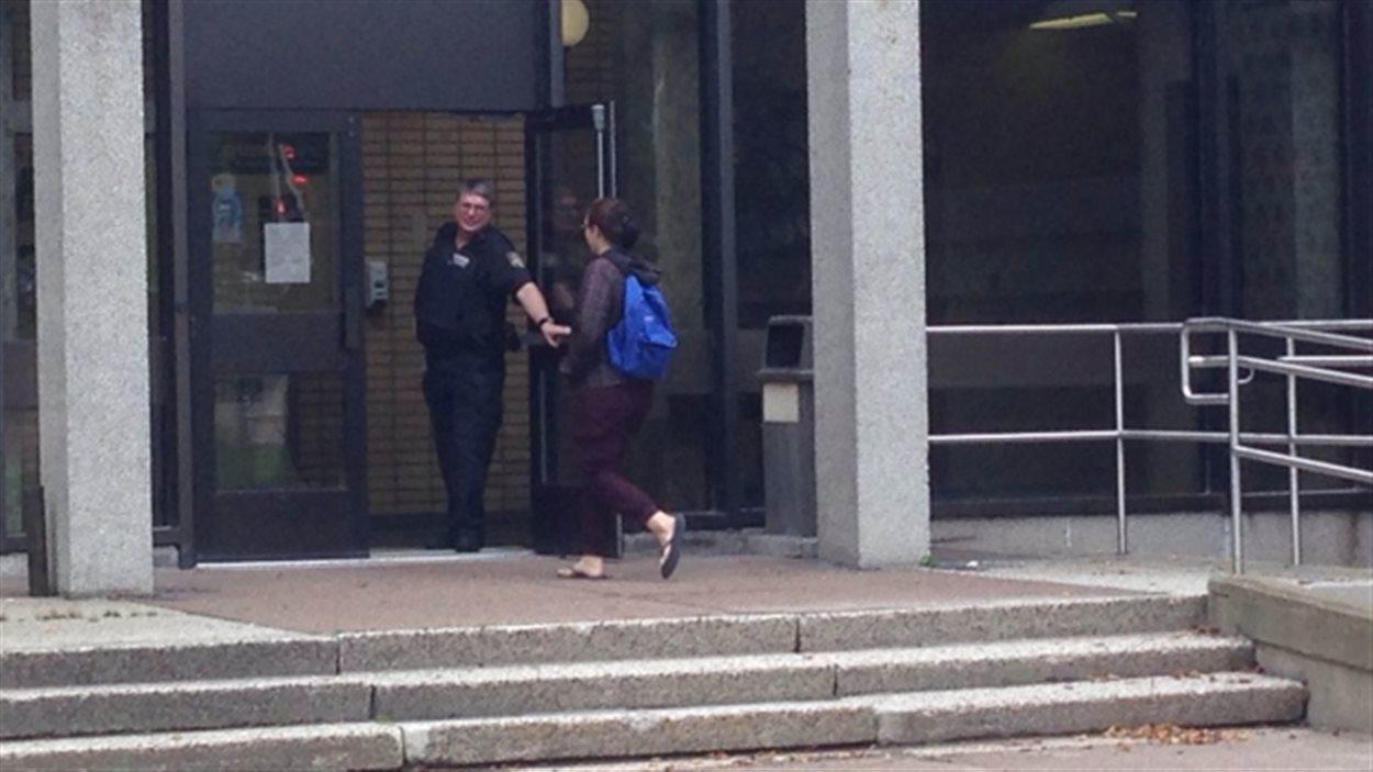 Un agent de sécurité ouvre la porte à une étudiante du département de médecine.