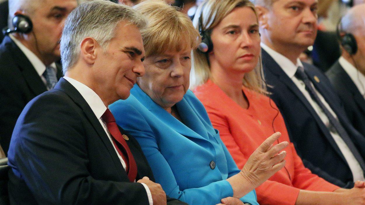 La chancelière allemande, Angela Merkel, parle à son homologue autrichien, Werner Faymann, à Vienne, le 27 août.