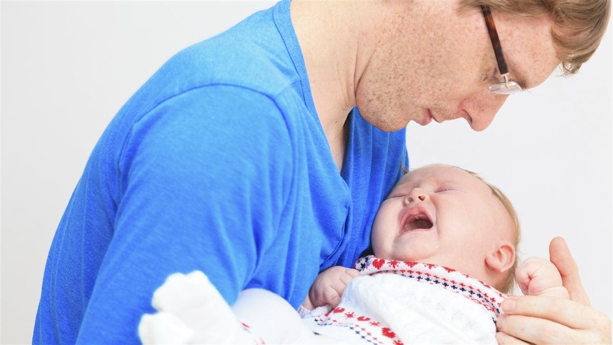 Un père regarde son bébé souffrir.