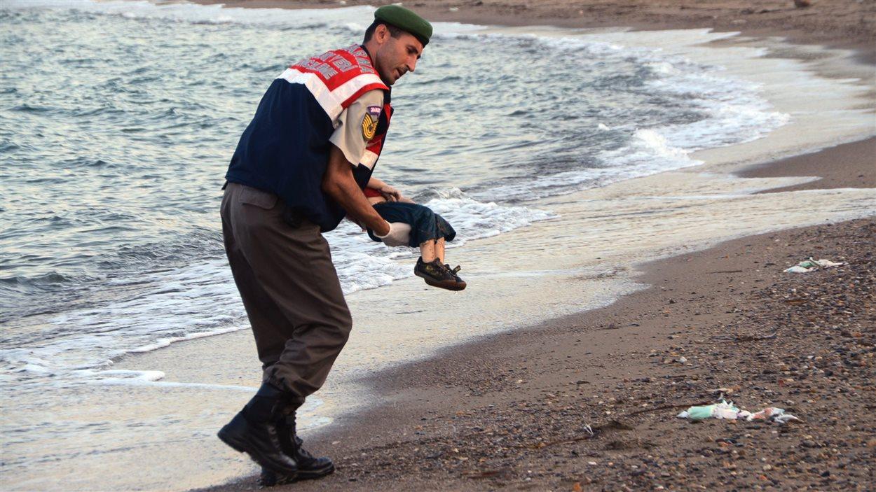 Un policier transporte le corps inanimé d'un enfant syrien.
