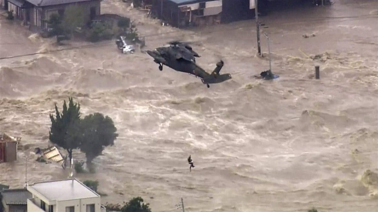 Un homme est secouru par un hélicoptère militaire à Joso au Japon.