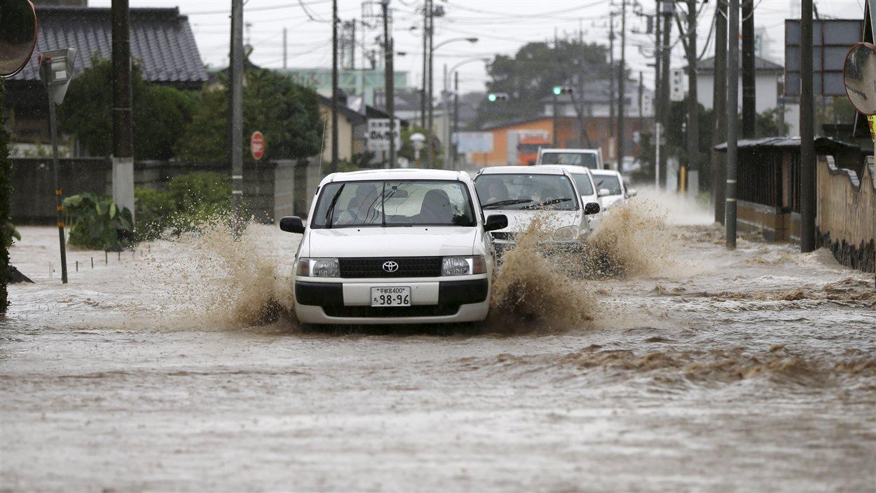 Des véhicules circulent dans un quartier résidentiel de Joso au Japon malgré l'état des rues innondées.