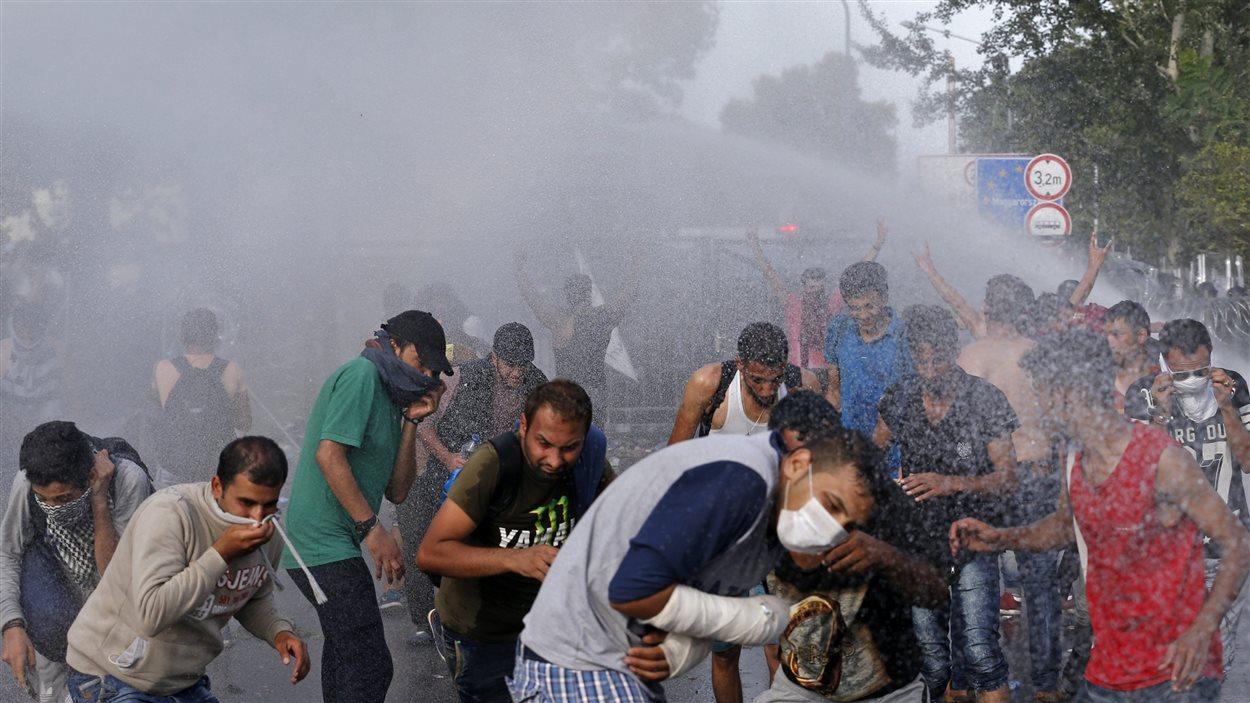 Les policiers hongrois utilisent des canons à eau, des gaz lacrymogènes et du gaz poivré pour refouler les migrants vers la Serbie.