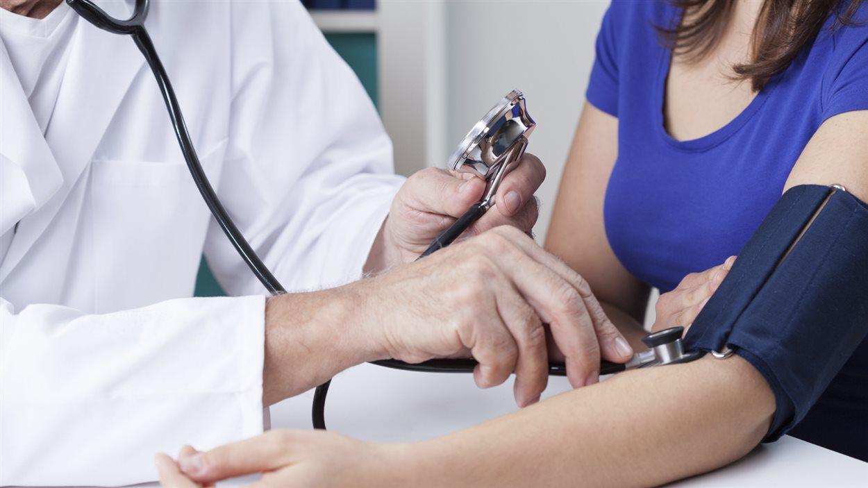 Un médecin mesure la pression artérielle d'une patiente.