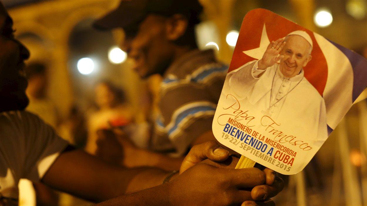 Un Cubain tenant une petite affiche souhaitant la bienvenue au Pape François.