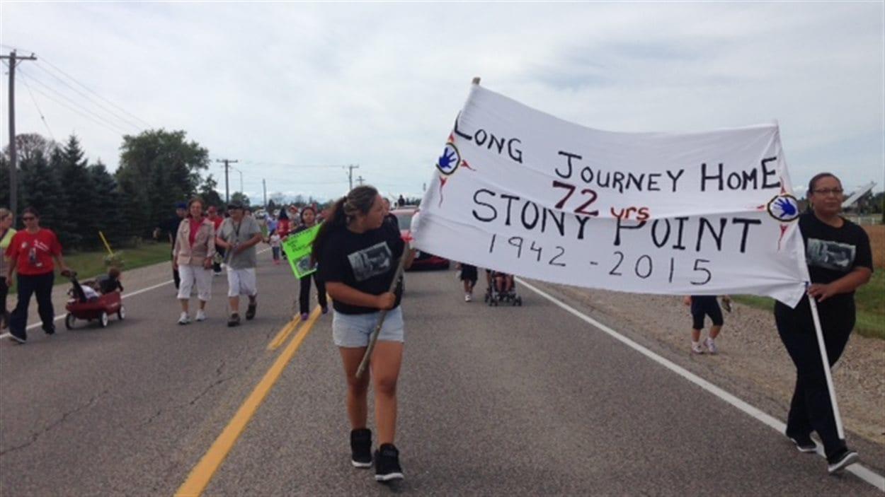 Des membres de la communauté marchent pour célébrer l'entente avec Ottawa.