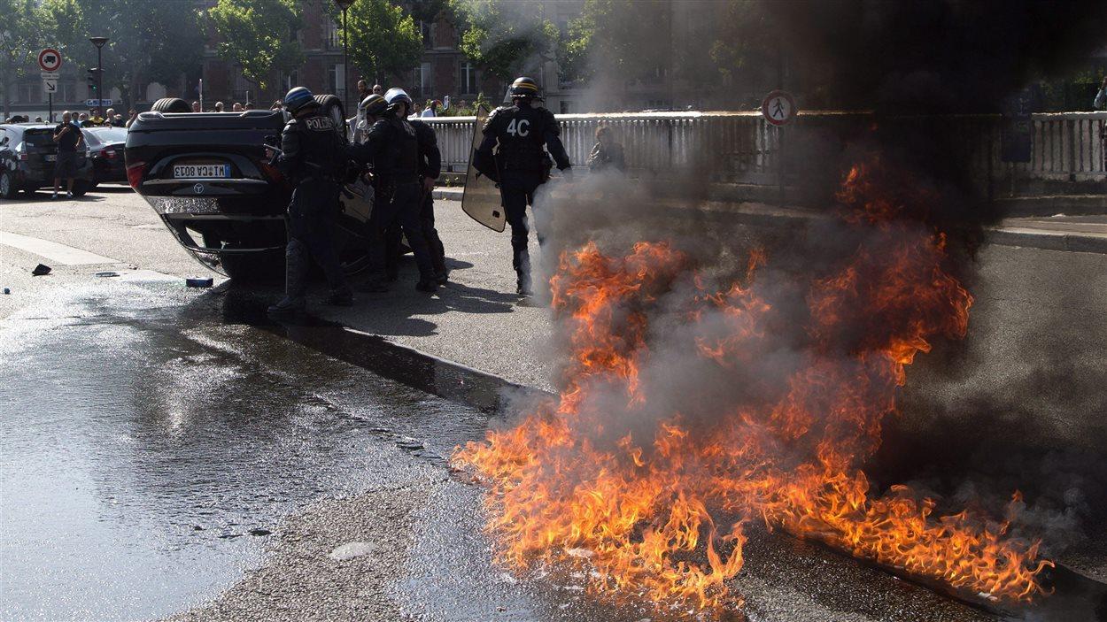 Véhicule renversé et flammes lors d'une manifestation anti-Uber de chauffeurs de taxi à Paris en juin dernier