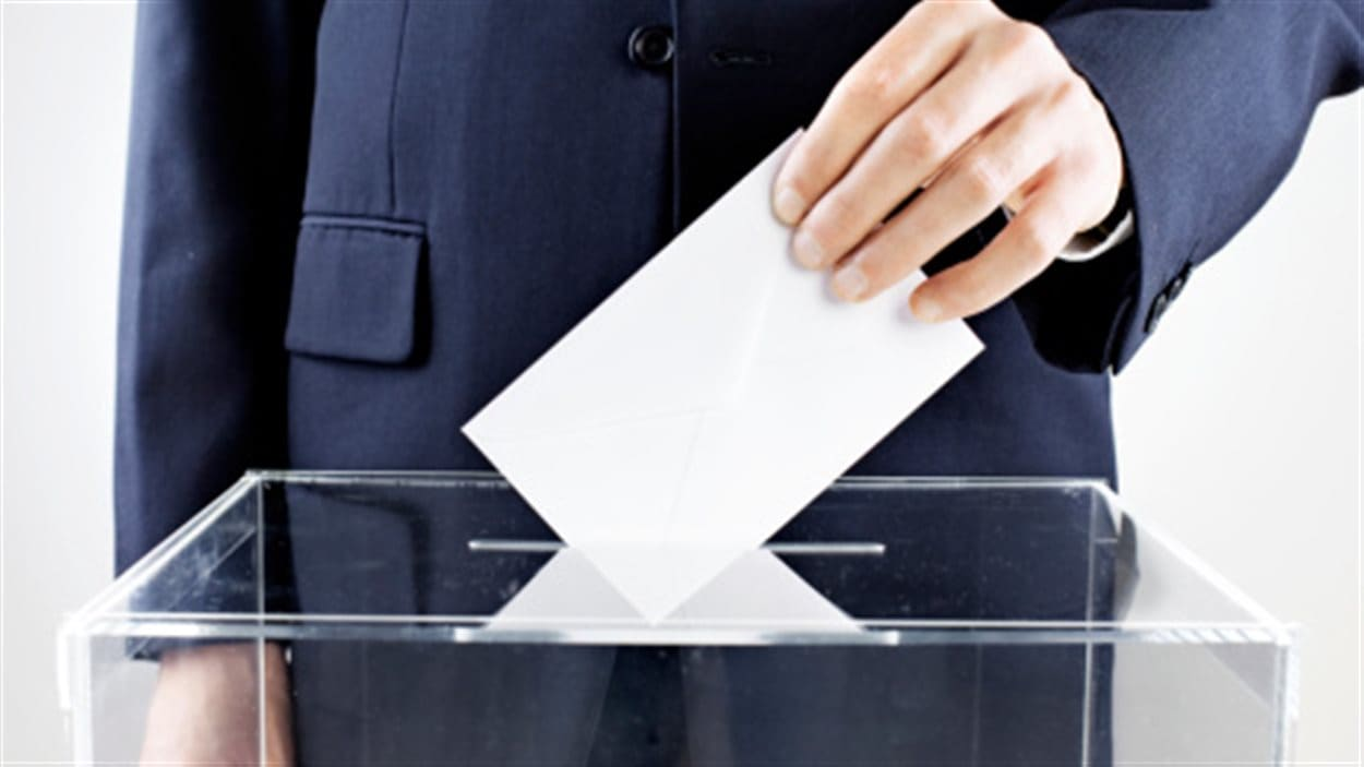 Un homme dépose son vote dans une urne de scrutin.