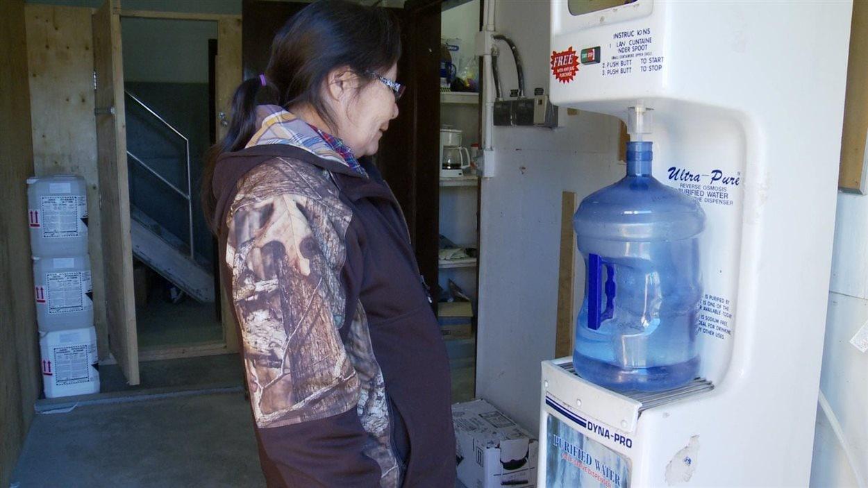 Maggie Sakanee vient remplir ses contenants d'eau plusieurs fois par semaine pour sa famille. Ils sont 6 à vivre dans sa petite maison d'une chambre à coucher.