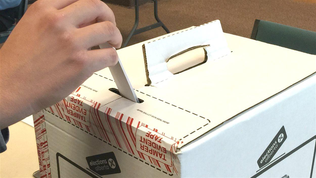 Une main place un bulletin de vote dans une urne.