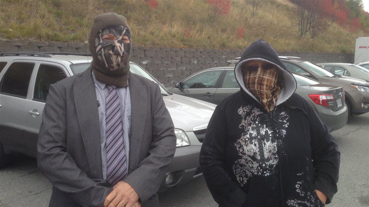 Deux personnes de Val-d'Or se présentent à leur bureau de vote par anticipation, le visage complèment couvert