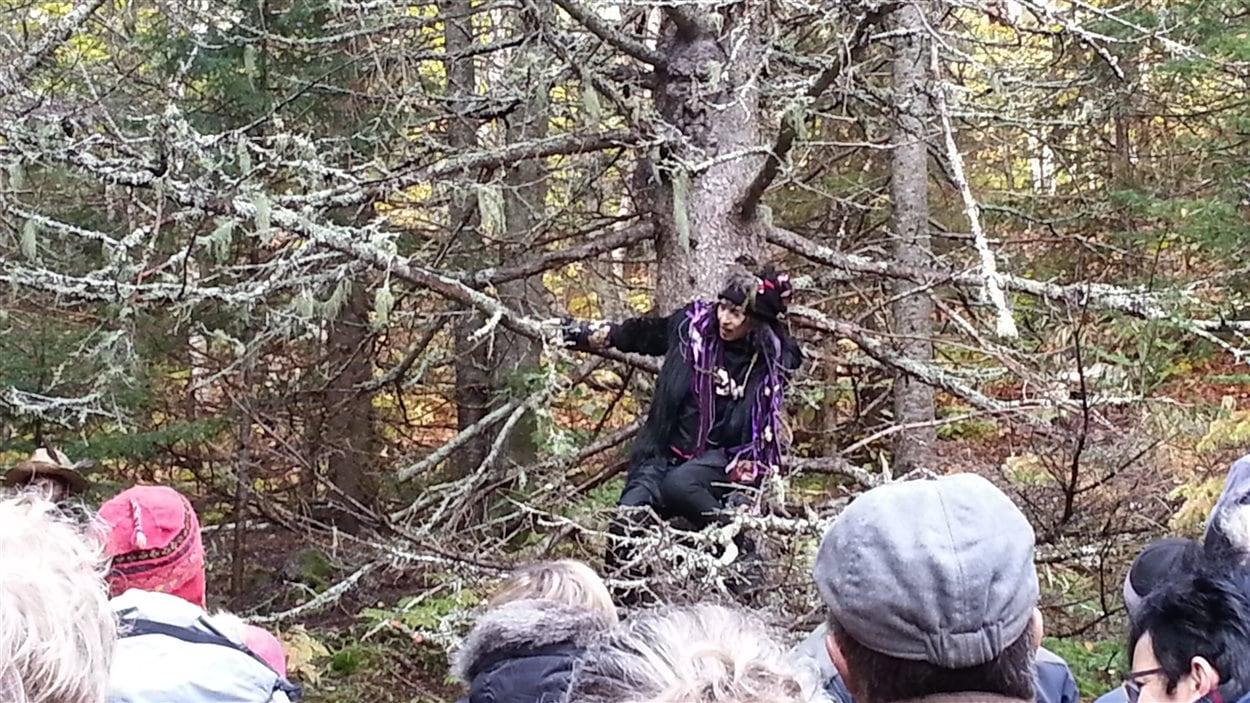 Myriam Pellicane s'adapte au sentier pour raconter. Les visages sculptés dans les arbres ajoutent à l'ambiance.