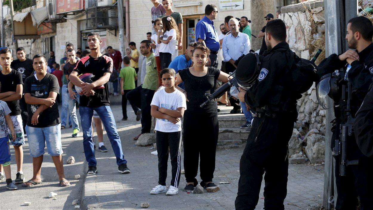 Des Palestiniens observent les forces de sécurité israéliennes qui ont installé un barrage dans un quartier de Jérusalem-Est.