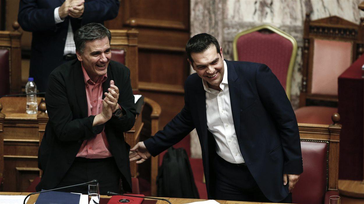 Le ministre grec des Finances, Euclid Tsakalotos, félicite le premier ministre Alexis Tsipras après un discours sur la nécessité d'adopter de nouvelles réformes.