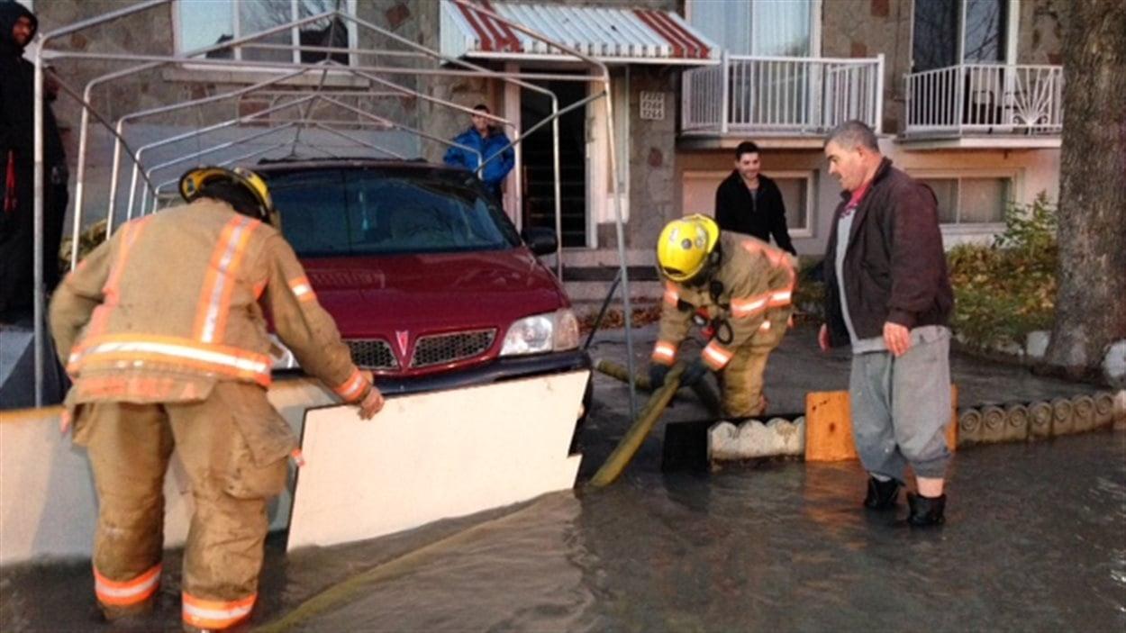 Des pompiers aident le propiétaire d'une maison inondée par le bris d'une conduite d'eau sur le boulevard Pie-IX.