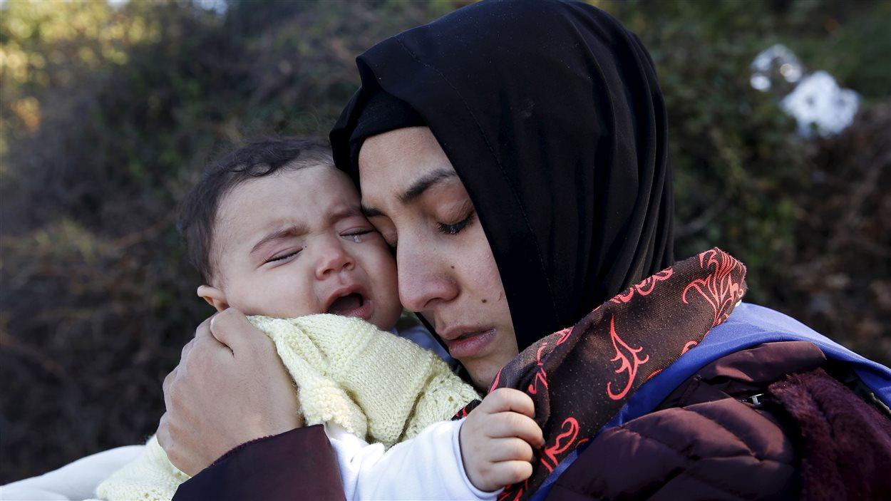 Une réfugiée syrienne enlace son bébé qui pleure, après être arrivée sur l'île de Lesbos à bord d'un radeau.