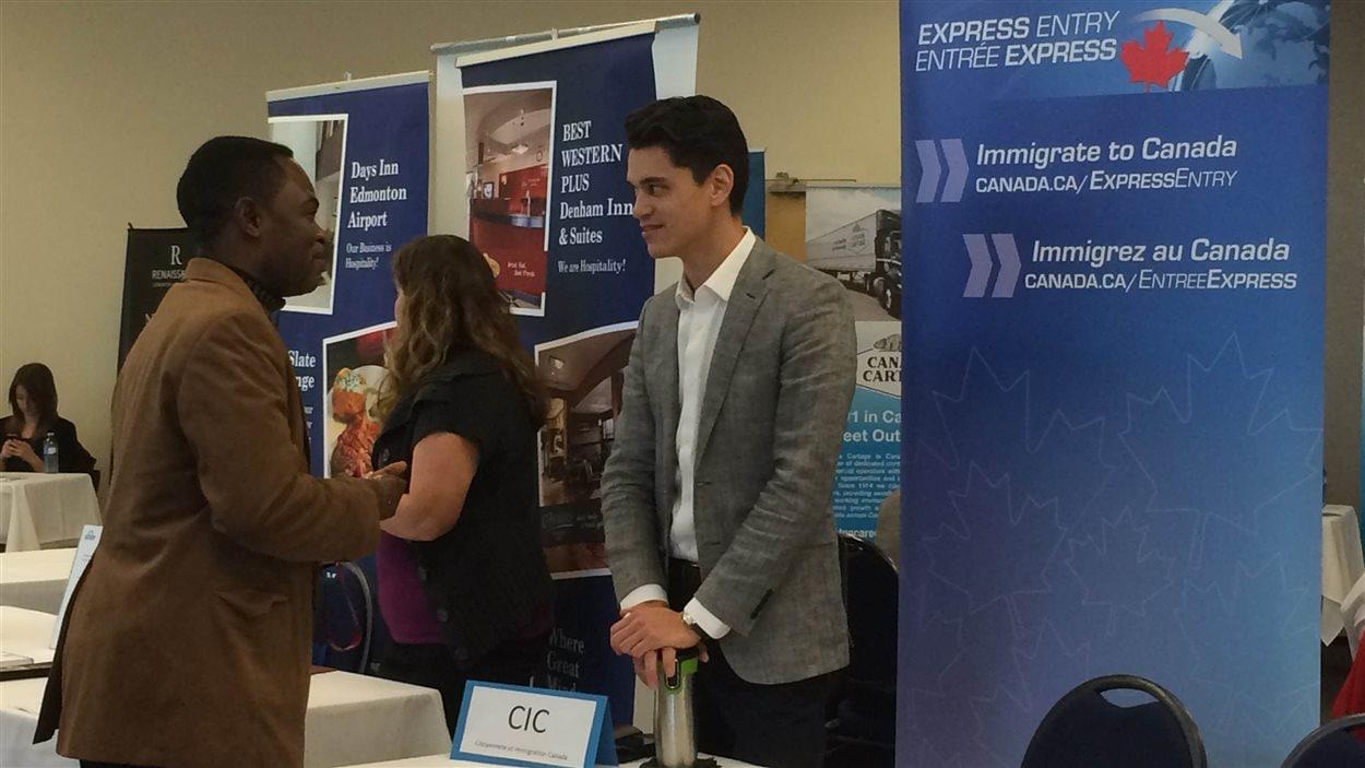 Un homme s'entretient avec un employé de CIC lors de la foire à l'emploi à La Cité francophone à Edmonton.