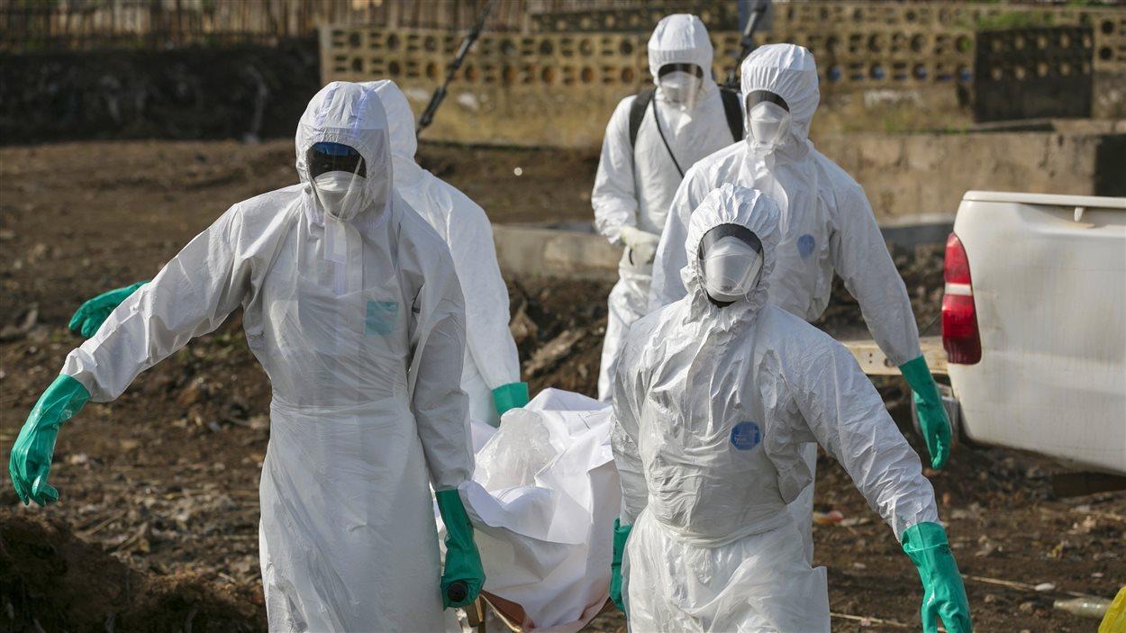Des travailleurs de la santé transportent la dépouille du victime de l'Ebola au Sierra Leone, décembre 2014