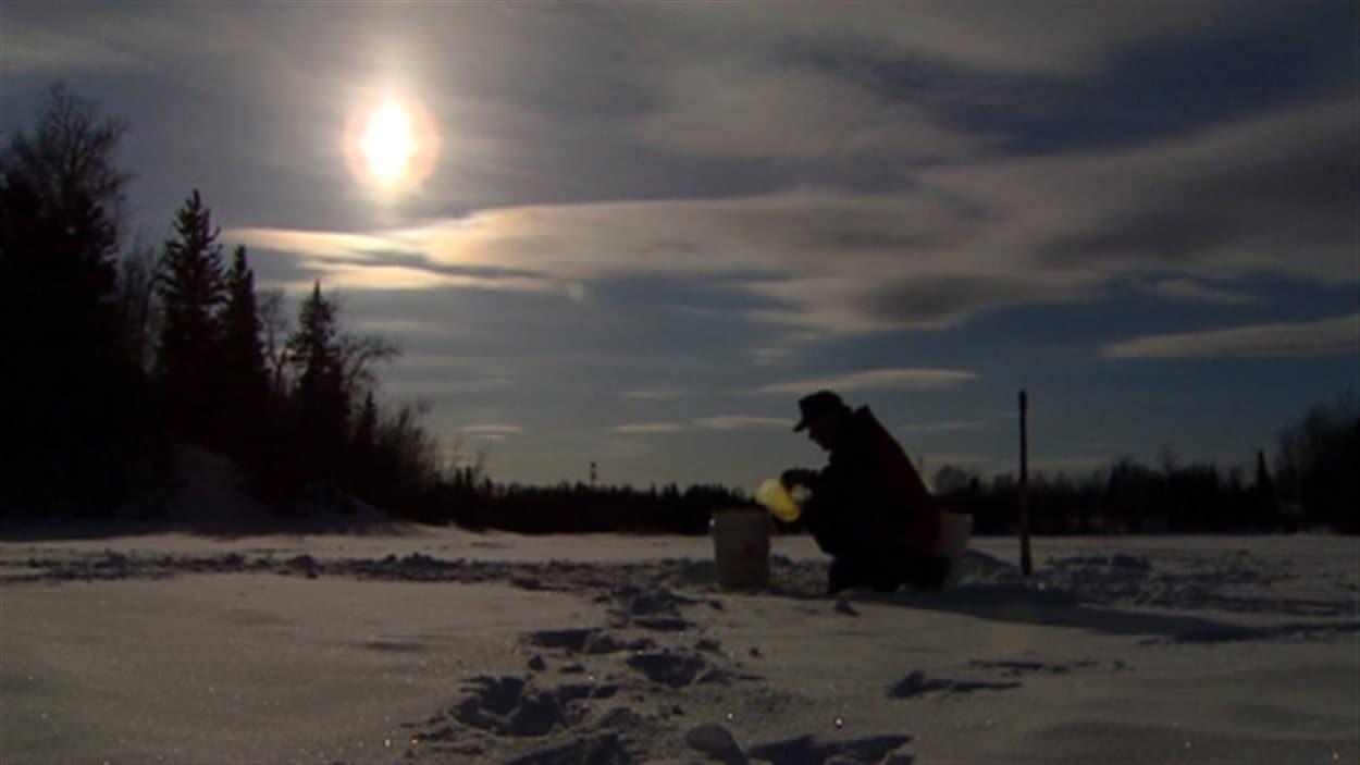 Un résident de la Première Nation Garden Hill puise de l'eau du lac.