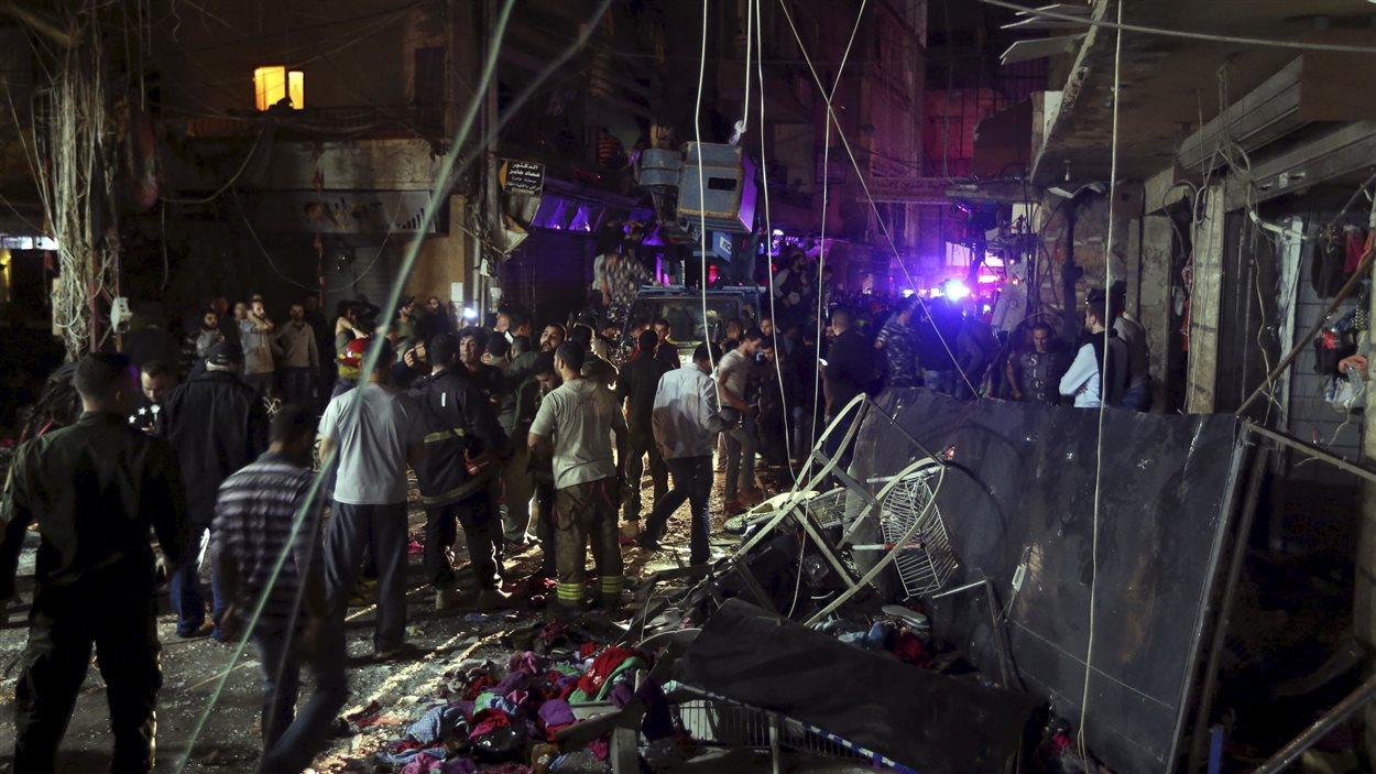 Des résidents constatent les dommages causés par le double attentat suicide dans un quartier de la banlieue sud de Beyrouth.